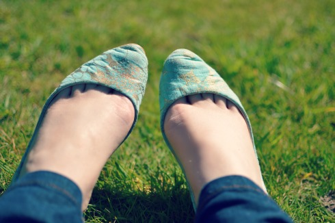 feet on grass with green shoes