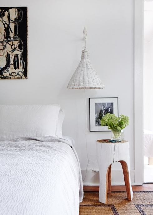 white bedroom with rattan wall light