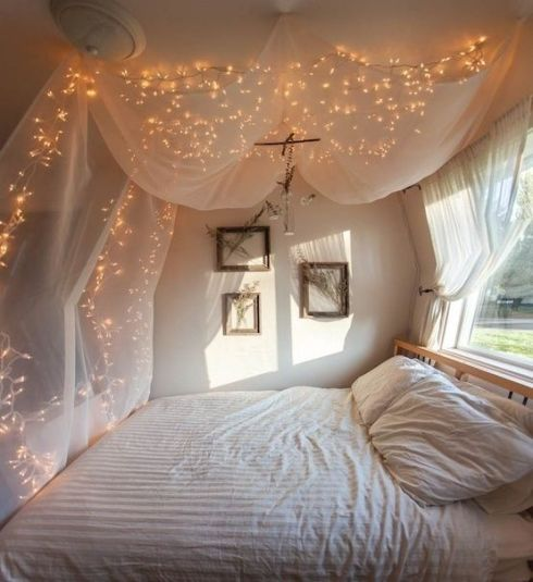 Fairy lights over bed curtains